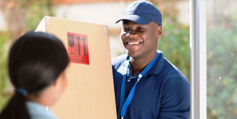 32518028 - friendly young african american delivery man delivering a package
